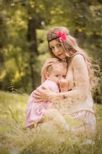 Sesja mamy karmiącej z dzieckiem przy piersi w plenerze.młoda matka karmiąca piersią córkę . Zdjęcie wykonał fotograf dziecięcy w Krakowie, Nowa Huta Prądnik Czerwony