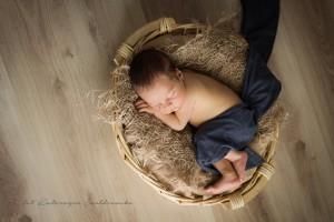 Zdjęcie noworodkowe Kraków osiedle złotego wieku. Noworodek chłopiec upozowany w koszyczku. Fotografia noworodkowa w stylu minimalistycznym.Newborn photography Cracow
