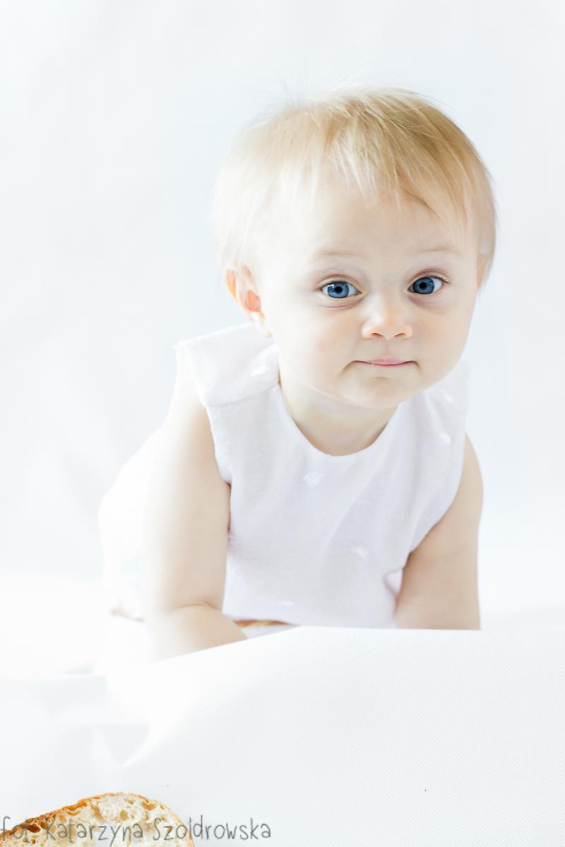 Fotografia dziecięca w Krakowie. Portret niemowlęcia dziewczynki na białym tle. Portret high key.